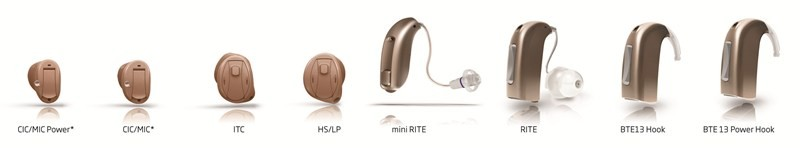 Eight hearing aids of varying sizes on white background